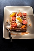 Waffle topped with sliced strawberries, orange and whipped cream