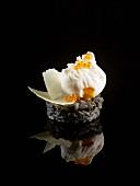 Schwarzes Risotto mit pochiertem Ei, Lachsrogen und Parmesanspänen auf schwarzem Hintergrund