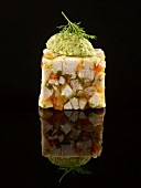 Rabbit and aspic terrine topped with a sorrel quenelle on a black background