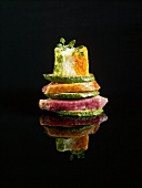 Layered duckling and zucchinis topped with a mini vegetable Bavarian on a black background