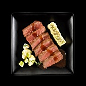 Fillet of beef with gravy,apple and potato mash and aniseeds on a black background