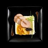 Gebratenes Schweinefilet auf Selleriepüree mit Bratkartoffeln und Pflaume auf schwarzem Teller