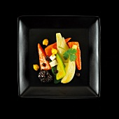 Vegetarian dish of stewed vegetables with dried fruit and vegetables on a black background