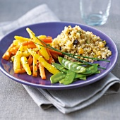 Vegetarian dish of sugar peas,carrot duo and quinoa with raisins