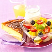 Fresh fruit salad,a slice of flan,a glass of orange juice and a yoghurt