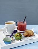 Kleingebäck mit Kaffee und einem Saftgetränk