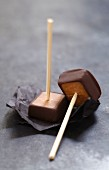 Chocolate coated toffees on sticks