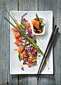 Salmon Sashimi with red cabbage and green sesame seeds