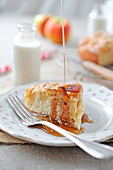 Pouring maple syrup over a slice of apple cake