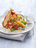 Multicolored tomato and feta salad with farmhouse bread crisps