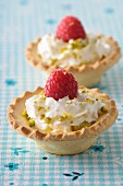 Whipped cream,crushed pistachio and raspberry tartlets
