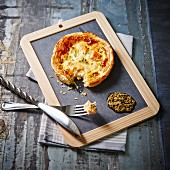 Individual salmon quiche and green tapenade on a slate blackboard
