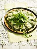 Grüne Pizza mit Pistazien und Rucola