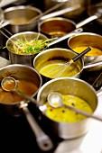 Saucepans of different sauces in a restaurant kitchen