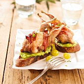 Roasted quail with bacon and tomato on guacamole toasts