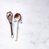 Wooden spoon and whisk coated in chocolate