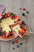 Serving a slice of cheesecake-style summer fruit tart