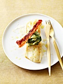 Pan-fried pike-perch with parmesan, spinach and mashed potato ball and a strip of fried bacon