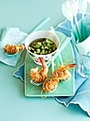 Fried scampis wrapped in noodles and a small bowl of chilled cucumber broth