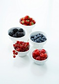 Bowls of summer fruit on a white background