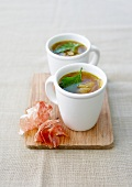Mugs of vegetable broth with raw ham