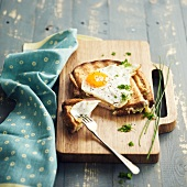 Cheese and ham toasted sandwich topped with a fried egg and sprinkled with herbs