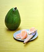 Grapefruitfilets auf kleinem Teller mit Messer, dahinter eine Avocado