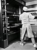 Bäcker holt das Brot aus dem Ofen