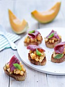 Crostini with diced melon and duck breast
