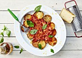Thinly sliced grilled zucchinis with tomato sauce and basil