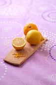 Zitronen ganz, halbiert und gerieben