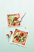 Mini-Pizza mit Zucchini, Tomaten und Pinienkernen