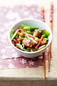 Japanese salad with caramelized pork and sesame seeds