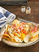 Fried eggs with potato crisps and raw ham