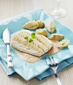 Pike fillet in creamy sauce and potatoes with parsley