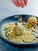 Covering the goat's cheese cake pops with crushed pistachios