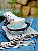 Dishes and cutlery on a table outdoors