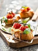 Crostini mit gebratenen Tomaten, geräuchertem Scamorza-Käse und Basilikum