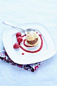 Chocolate mousse cream puff with raspberry coulis