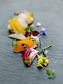 Palette mit Poutargue (Rogen der Meeräsche) mit knackigem Gemüse und Essblüten