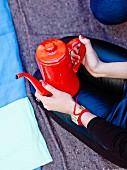 Person holding a tin teapot