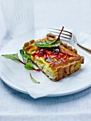 Portion of courgette,red onion chutney and beetroot leaf quiche