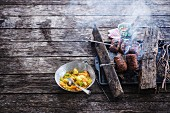 Cooking turkey sausages on the barbecue,curried semolina with vegetables