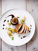 Thick turkey fillet with pear stewed in red wine and garnished with whipped cream