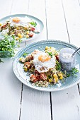 Quinoa salad with tomatoes, yellow peppers, fried egg and cottage cheese