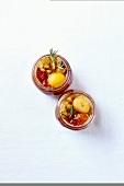 Eingemachte gelbe Pflaumen mit Tomaten, Sultaninen und Rosmarin in Einmachgläsern