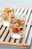 Nudelsalat mit Tomaten, Sardinen und Oliven, in Gläsern serviert