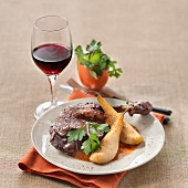 Braised duck curry with poached pears, glass of red wine