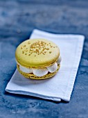 A macaroon with golden sprinkles