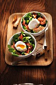 Corn lettuce and smoked salmon salad garnished with a soft-boiled egg